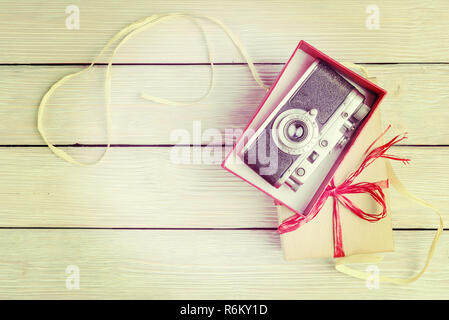 Vintage camera in red gift box, top view. Instagram filtered. - Stock Photo