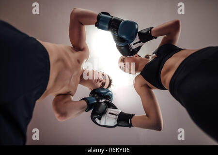 Low angle view of man and woman at kick boxing fighting position. Male and female kick boxers standing against each other with boxing gloves in ring. - Stock Photo
