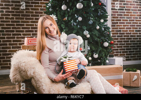 Theme Christmas holidays winter new year. A young stylish Caucasian mother holds her son in her arms for 1 year in a funny shirt sitting on a sleigh and wearing fur under the tree of decorated house - Stock Photo