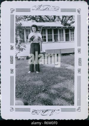 Woman standing on the lawn of a suburban home and holding a Kodak Brownie box camera, an iconic early 20th century camera, printed with an ornate decorated frame, August, 1947. () - Stock Photo