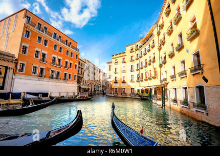 Landscape with gondolas and colorful buildings along canal in Venice at sunny day. Italy