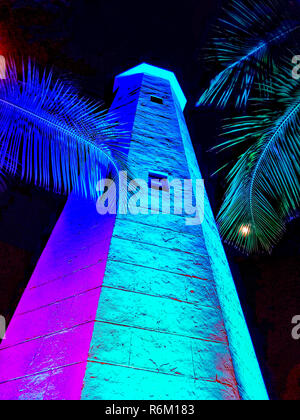 Night view with colored lights of Needham's Point lighthouse, located on the southwest coast of Barbados on Hilton property. Full moon can be seen through palm fronds. It is one of four still existing historic lighthouses in Barbados. The octagonal lighthouse was constructed in 1855 at the southern end of Carlisle Bay. It is currently non-functional and partially restored by the Hilton Hotel which owns the lighthouse and surrounding grounds. - Stock Photo