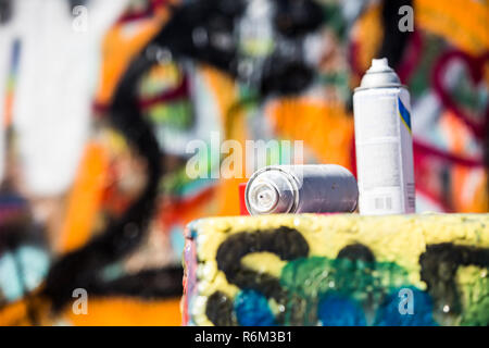 Two Discarded Spray Cans in Front of Graffiti Wall - Stock Photo