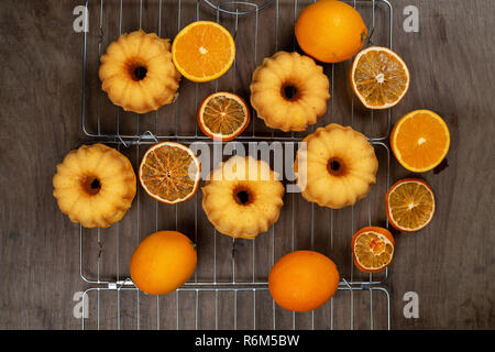 Small orange bundt cakes with fresh and dry oranges on cooling ruck, top view, flat lay - Stock Photo