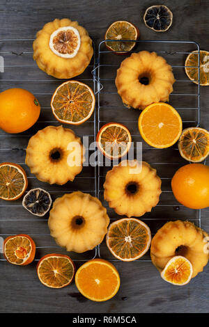 Small orange bundt cakes with fresh and dry oranges on cooling ruck, top view, flat lay, vertical composition - Stock Photo