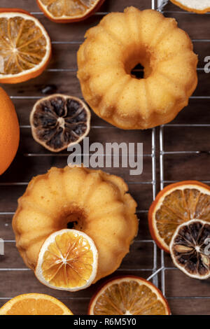 Small orange bundt cakes with fresh and dry oranges on cooling ruck, top view, flat lay, close up,  vertical composition - Stock Photo