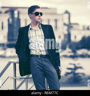 Young handsome business man in sunglasses in city street Stylish male model in black blazer - Stock Photo