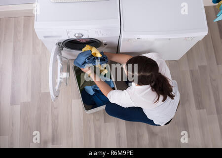 Elevated View Of A Woman Loading Clothes In Washing Machine - Stock Photo