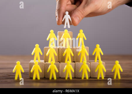 Person Placing White Human Figure Standing On Top - Stock Photo