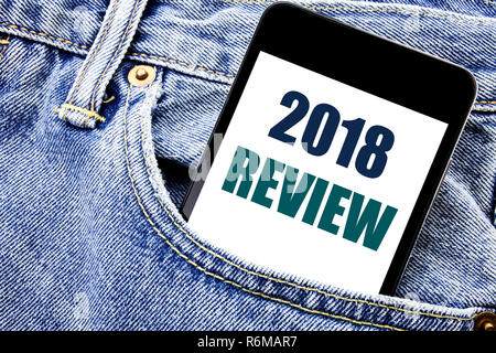 Conceptual hand writing text caption inspiration showing 2018 Review. Business concept for Feedback On Progress Written phone mobile phone, cellphone placed in the man front jeans pocket. - Stock Photo