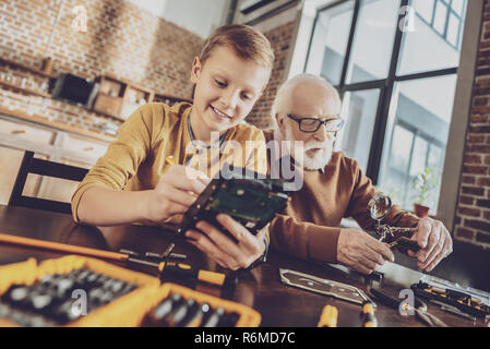 Kind boy trying to repair radio - Stock Photo