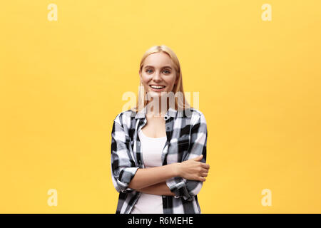 Confident business expert. Beautiful young woman in smart casual wear keeping arms crossed and smiling while standing against yellow background - Stock Photo