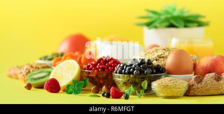 Organic food frame. Banner. Healthy breakfast ingredients. Oat and corn flakes, eggs, nuts, fruits, berries, toast, milk, yogurt, orange, banana, peac - Stock Photo