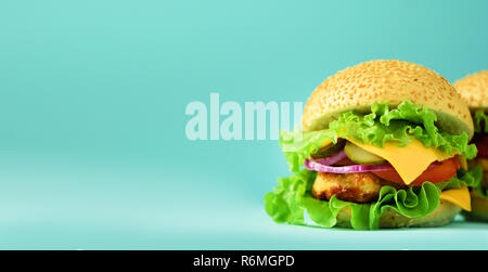 Fast food banner. Juicy meat burger, french fries potatoes and cola drink on blue background. Take away meal. Unhealthy diet concept with copy space. - Stock Photo