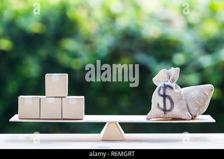 Money and supply concept : Money dollar bag and supply products on balance scale on wooden table depicts balancing between risk and return. Investment - Stock Photo