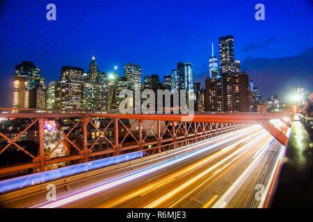 Buildings and transportation on Brooklyn bridge in night New York. - Stock Photo