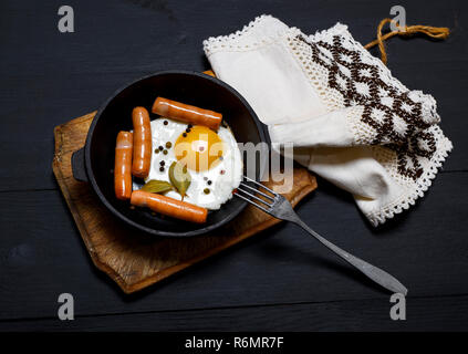 fried eggs and sausages in a black frying pan - Stock Photo