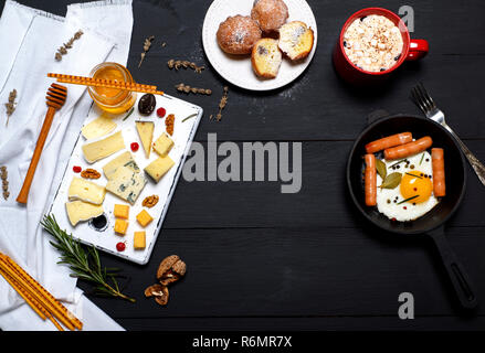 fried eggs with sausages in a frying pan and types of cheese - Stock Photo