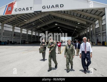 Congressman Charlie Crist, U.S. Representative for Florida's 13th District, right, speaks with Air Station Clearwater crew members Tuesday, May 30, 2017, prior to an aerial assessment of beach erosion along Pinellas County, Florida's coast. Coast Guard Air Station Clearwater MH-60 Jayhawk helicopter crew members provided the overflight for the congressman and Army Corps of Engineers personnel. U.S. Coast Guard by Petty Officer 1st Class Michael De Nyse - Stock Photo