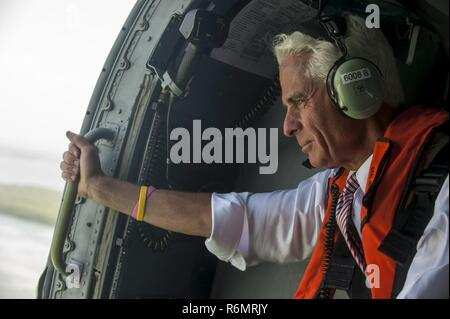 Congressman Charlie Crist, U.S. Representative for Florida's 13th District, keeps a eye on the coastline during an aerial assessment of beach erosion along Pinellas County, Florida's coast, Tuesday, May 30, 2017. Coast Guard Air Station Clearwater MH-60 Jayhawk helicopter crew members provided the overflight for the congressman and Army Corps of Engineers personnel. U.S. Coast Guard by Petty Officer 1st Class Michael De Nyse - Stock Photo