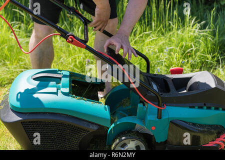 Close up on man emptying the catch basket of an electro lawnmower - Stock Photo