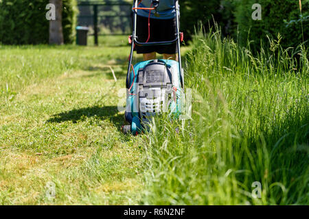 Man cutting grass with  an electro lawnmower in his garden - Stock Photo
