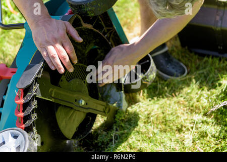 Close up on man cleaning an electro lawnmower - Stock Photo