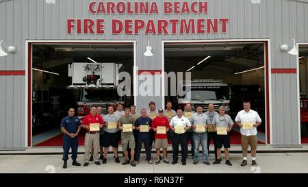 Personnel from New Hanover and Brunswick County agencies hold up their Boat Crew Member certifications after graduating a course taught by Station Oak Island personnel May 8, 2017, in Oak Island, North Carolina. Pictured front row from left to right: Master Chief Petty Officer Mark Kannan, Winston C. Soward, Benjamin Bobzien, Jonathan E. McDade, Marc A. Sestrich, Edmund C. Kennedy, Buddy R. Thompson Jr., Fire Chief Simon W. Sanders, Alan Griffin and Chris R. Ward. Pictured back row from left to right: Carl Mauney, Tyler Crouch, Kevin R. McDonald, Courtney S. Padgett, Anders S. Remahl, Eric G.