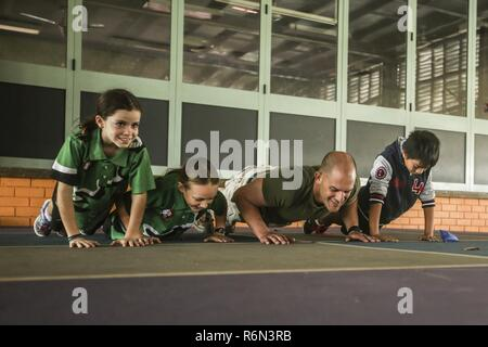 DARWIN, Australia – U.S. Marine Staff Sgt. Bret Daneker, platoon sergeant, Company I, 3rd Battalion, 4th Marine Regiment, 1st Marine Division, Marine Rotational Force Darwin, does Marine Corps Push-Ups with students during a volunteer event, May 31, 2017. The same group of Marines will continue visiting and mentoring the students throughout their time in Darwin. The Marines are committed to serving the local community and will continue to make an impact when available. - Stock Photo