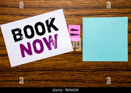 Handwriting Announcement text showing Book Now. Business concept for Reservation Buy Booking written on sticky note paper on wooden background. Equation mathematical sign for your space - Stock Photo