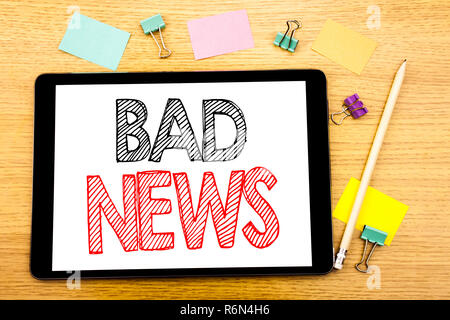 Writing text showing Bad News. Business concept for Failure Media Newspaper Written on tablet laptop, wooden background with sticky note and pen - Stock Photo
