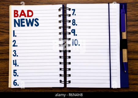 Writing text showing Bad News. Business concept for Failure Media Newspaper Written on notebook note paper, wooden background with pen and marker. - Stock Photo