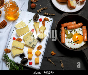 black cast-iron frying pan with one fried egg and sausages - Stock Photo