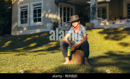 Little cowboy sitting outdoors in backyard with water pistol. Young boy wearing cowboy hat with water squirt gun. - Stock Photo