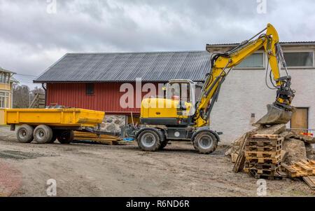 FLODA, SWEDEN - NOVEMBER 21 2018: Medium sized yellow excavator with trailer resting it's bucket on pile of wood pallets - Stock Photo