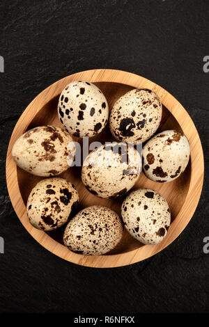 Quail eggs in a wooden bowl, shot from the top on a black background with a place for text - Stock Photo