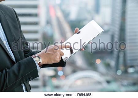 businessman and a city using a tablet over white background - Stock Photo