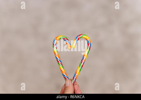 Two candy canes making a heart on textured background, Candy cane heart in female hand.Candy Canes colorful in the Heart Form Lie on the grey Background. Decoration of Postcards, New Year and Christmas. Place for Text. - Stock Photo
