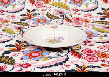 flower plate hidden on a flowery fabric - Stock Photo