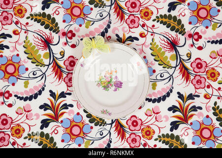 flower plate hidden on a flowery fabric with a yellow butterfly - Stock Photo