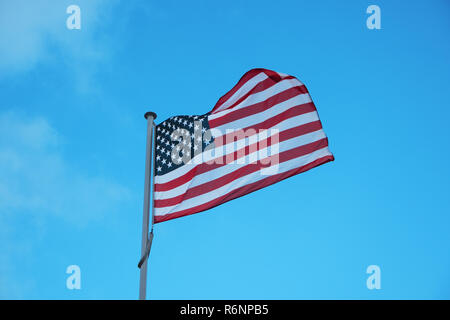 Flag of USA waving in wind on blue sky background - Stock Photo