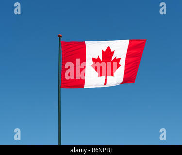 Flag of Canada waving in wind, blue sky background - Stock Photo