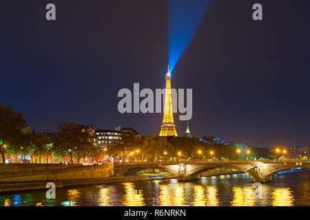 PARIS, FRANCE - NOVEMBER 10, 2018: Siene river embankment and Eiffel Tower with spotlight at night in Paris. - Stock Photo