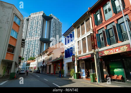 Restored shophouses in Keong Saik Road in Chinatown, Singapore , in the background The Pinnacle@Duxton, an award winning HDB housing complex - Stock Photo