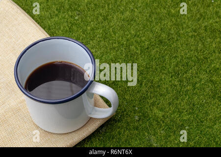 Coffee in white tin cup on grass background. - Stock Photo