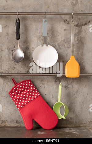 Kitchenware hanging on stainless rail on cement wall background. - Stock Photo