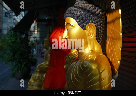 A Buddha statue outside a factory for Buddha statues in Bamrung Muang Road, Bangkok, Thailand, is illuminated by the first rays of the rising sun - Stock Photo