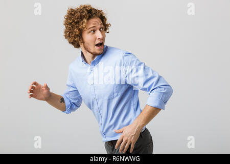 Portrait of a scared young man with curly hair isolated over white background, running away - Stock Photo