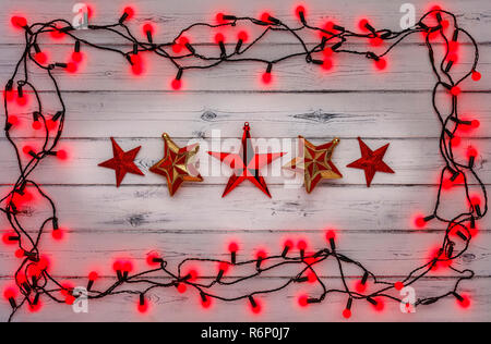 A string of red holly berry christmas lights, and a row of red stars, on a destressed woodern background - Stock Photo