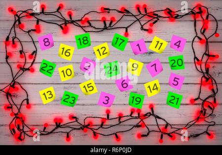 Advent numbered parer notes, with a border of red holly berry christmas lights, on a distressed white wooden board - Stock Photo